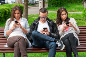 Group of people sitting on a bench staring at their phones